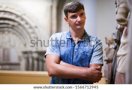 man visiting exposition of historical museum with exhibits of antiquity