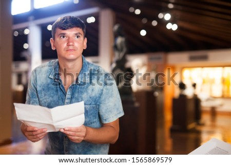 Man visiting historical museum, looking at exhibits and holding information leaflet