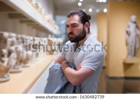 Man visiting sculpture hall in historical museum and looking at exhibits
