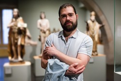 Man visiting sculpture hall in historical museum and looking at exhibits. High quality photo