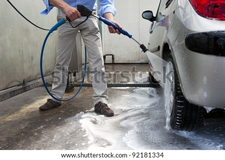 Man, wahsing his car in the stall of a car wash, using a high pressure water jet - stock photo