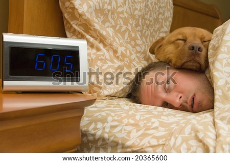 Man waking up with dog comfortably sleeping in
