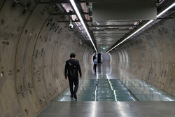 Man walk at underground tunnel.Transport walkway by Tunnel Boring Machine for infrastructure subway with raw concrete segments wall. Light at the end of the tunnel.