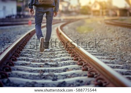 Man walk away on railroad with warm light.Selective focus.Traveler man on railroad.