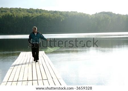 man walking alon pier with fishing nets in hands