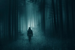 Man walking alone in magical dark turquoise green colored foggy artistic forest landscape.
