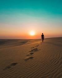 Man walking alone in the dunes of the desert
