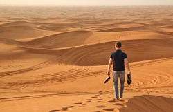 Man walking alone in the sunny desert near Dubai