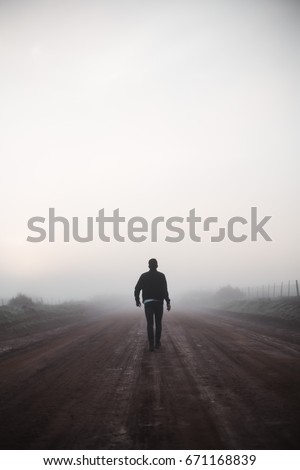 Man walking alone on misty road #671168839