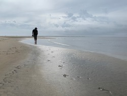 Man walking along a deserted shoreline under a moody sky, while leaving footprints in the sand