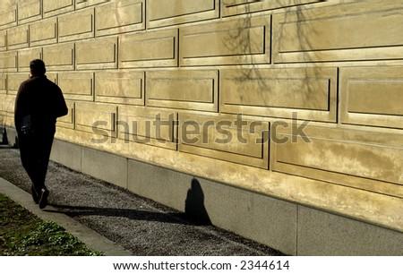 man walking along the wall