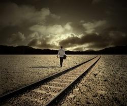 man walking along train tracks