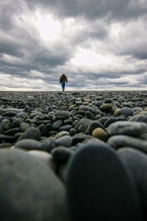 man walking at beach with stones dramatic sky clouds