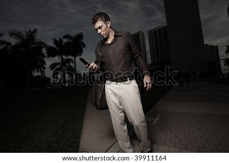 Man walking at night and dialing his phone