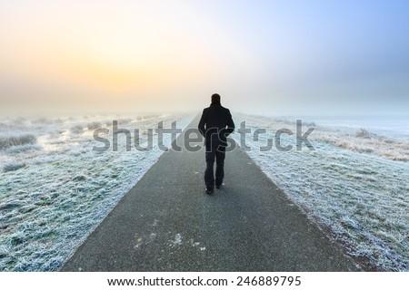 Man walking away on an empty desolate raod
