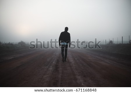 Man walking away on misty road