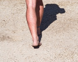 Man walking barefoot at the Lighting in a Bottle music festival in Bradley California. May 2016.