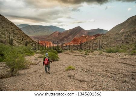 man walking between the Purmamarca hills, Quebrada de Huamahuaca, Jujuy, Argentina, with a backpack on his back #1345601366