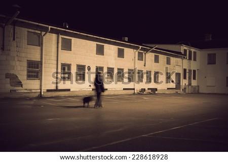 Man walking black dog in depressing industrial area
