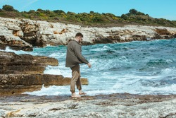 man walking by rocky beach in windy day summer vacation. enjoy sea view. summer time