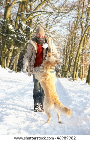 Man Walking Dog Through Snowy Woodland