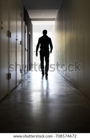 Man walking down a corridor towards a well lit end/exit #708574672