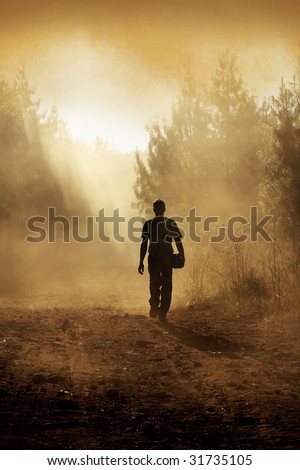 Man walking down gravel road after a forest fire
