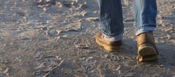 Man walking forward on sand, moving feet with leather boots and rolled up jeans, leisure activity or working concept, selected focus, narrow depth of field