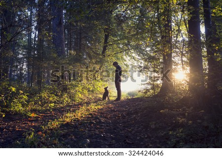 Man walking his dog in the woods standing backlit by the rising sun casting a warm glow and long shadows.