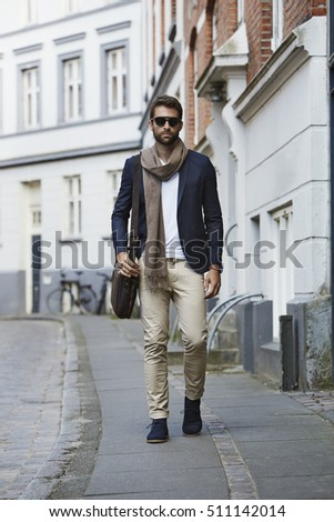 Man walking in city wearing sunglasses and scarf
