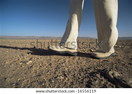 Man walking in desert, low section