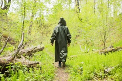Man walking in rain coat on background of wet forest. Healthy lifestyle. Green summer nature. Man walking  in raincoat. Rain in forest. Dark raincoat. Extreme vacation. Journey on summer nature.