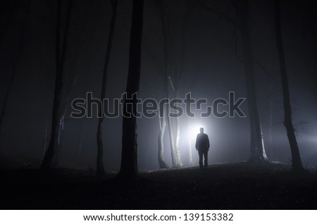 man walking in spooky forest at night