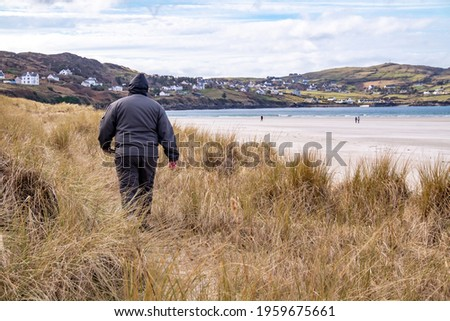 Man walking in the dunes at Portnoo, Narin, beach in County Donegal, Ireland. Stok fotoğraf ©