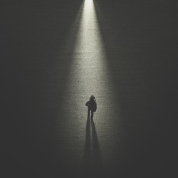 man walking in the night toward a cone of light
