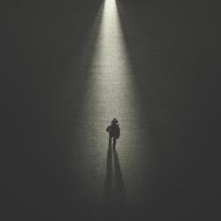 man walking in the night toward a cone of light