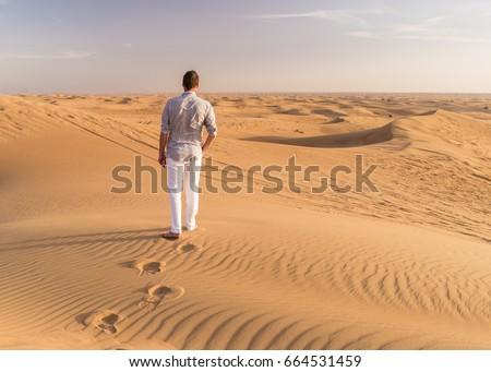 Man walking in the Yellow desert dunes and sky,Red sand Arabian desert near Dubai, United Arab Emirates,Huge dunes of the desert #664531459