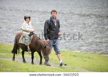 Man walking near a little boy sitting on a pony at a lakeside