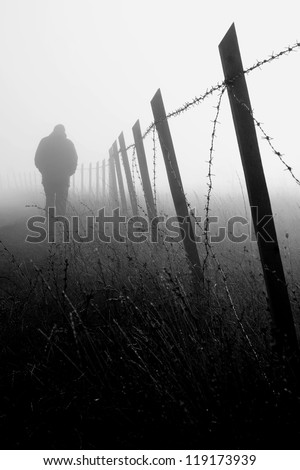 Man walking near barbed wire fence in dense fog