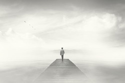 Man walking on a boardwalk in the fog