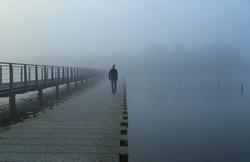 Man walking on a footbridge into the morning fog.