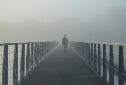 Man walking on a footbridge into the morning fog.