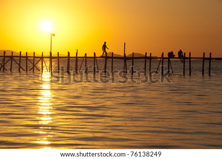Man walking on a wooden bridge over a tropical sea