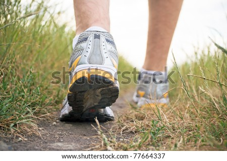 Man walking on footpath, sports shoe closeup, exercise outdoors. Running or jogging outside in summer nature, fitness and health concept