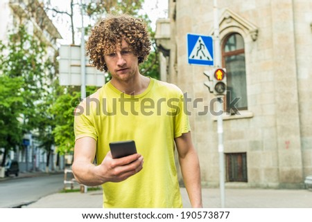 Man walking on red light on crossroad while watching in phone