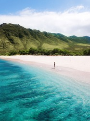 Man walking on the beach - Tropical paradise beach with white sand and mountain background travel tourism wide panorama background. Hawaiian beach. Oahu.