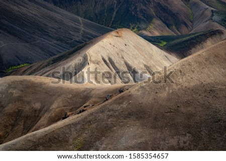 Man walking on the path on the colorful hill with black ash ob background in the Laugavegur hiking trail. Landmannalaugar, Iceland. Concept of peaceful, concentration and calm