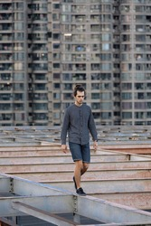 Man walking on the rooftop, wearing casual, curly hair collected in the pony tail. Background of residential building. Urban rooftopper extreme lifestyle, cityscape, abandoned atmosphere