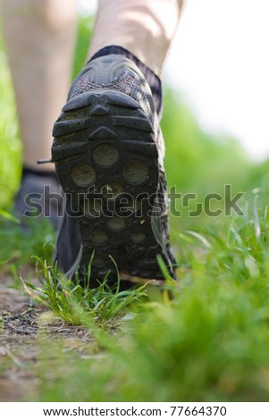 Man walking or running in green summer forest, exercise outdoors. Jogging or training outside in summer nature, motivational health and fitness concept. - stock photo