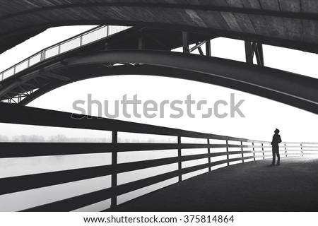 man walking outdoor under bridge